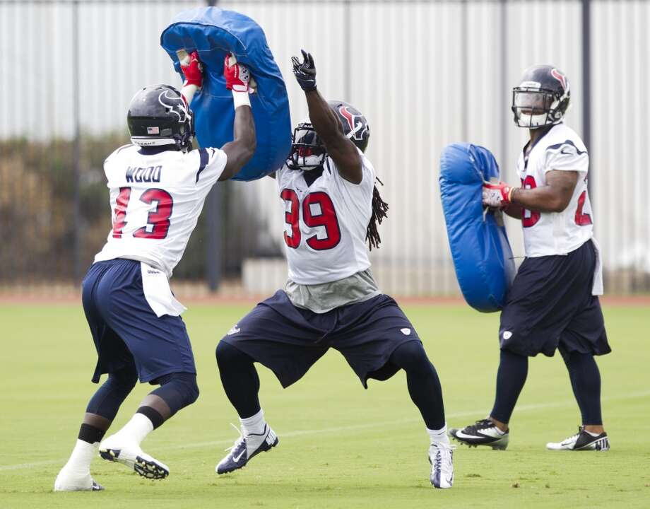 Texans running backs Cierre Wood (43), Deji Karim (39) and Dennis Johnson (28) run through blocking drills.