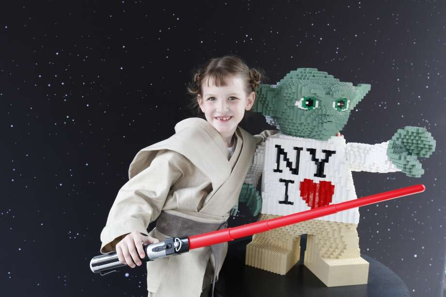Jocelyn Clera Watwood poses with a LEGO sculpture of Yoda after the unveiling of the world's largest Lego model in New York City's Times Square, Thursday May 23, 2013.