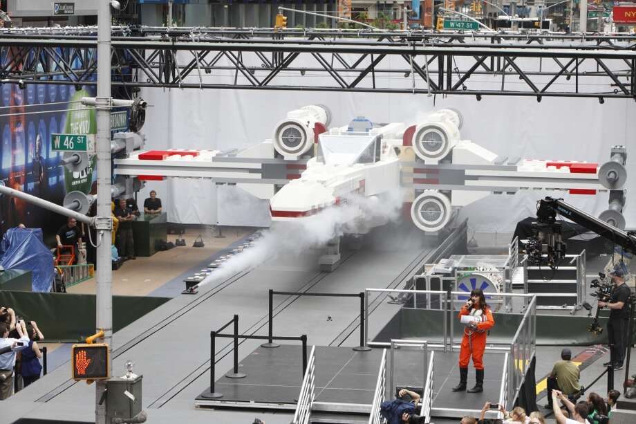 Thousands gather in New York City's Times Square to watch the unveiling of the world's largest Lego model, a 1:1 replica of the Lego Star Wars X-wing Starfighter.