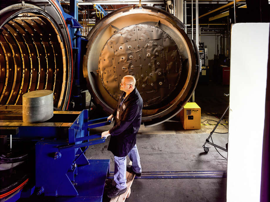 A worker loads a container holding ceramic matrix composites (CMC) components inside a high-pressure autoclave for curing. Ceramic parts will help improve the fuel efficiency of jet engines, according to GE. Photo: Contributed Photo/GE