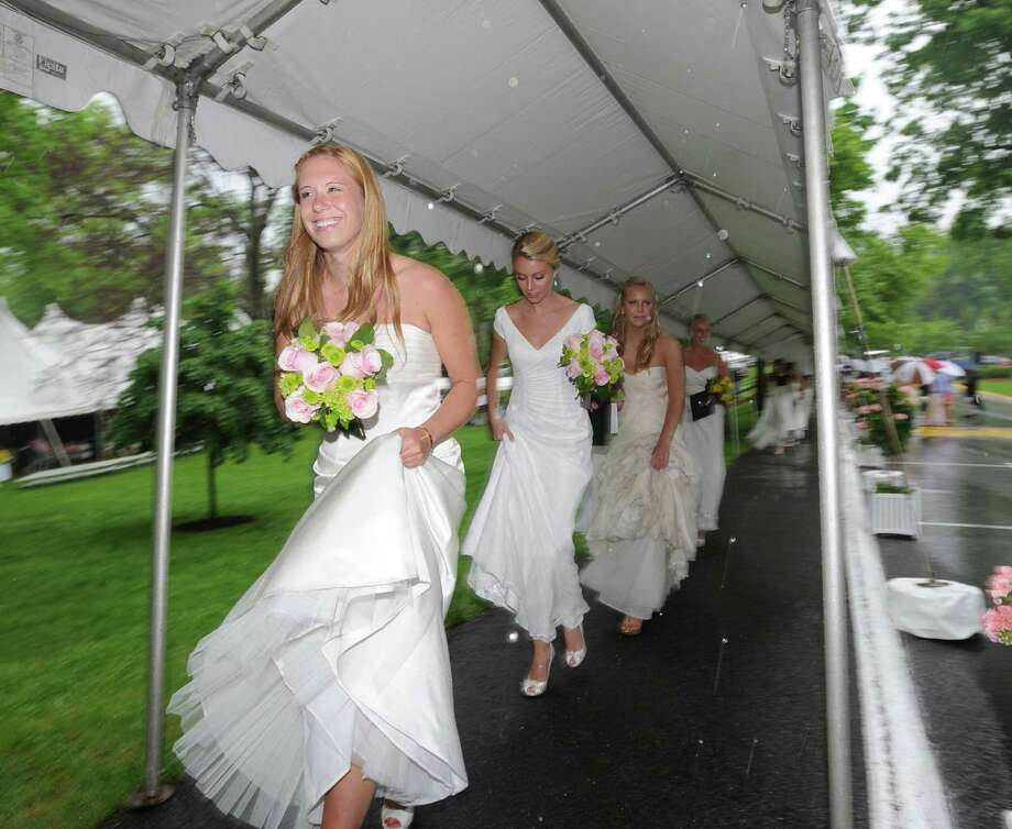 At left, Caroline King, leads fellow Greenwich Academy graduates from the commencement ceremony while pulling up her dress and walking under an awning during a downpour at the conclusion of the graduation ceremony at the school in Greenwich, Thursday, May 23, 2013. Photo: Bob Luckey / Greenwich Time