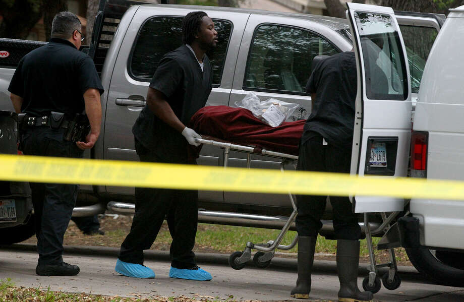 A man's body is loaded into a van in the 8900 block of Hambledon Drive after he was fatally shot. The man had been threatening people inside a home. Photo: John Davenport / San Antonio Express-News