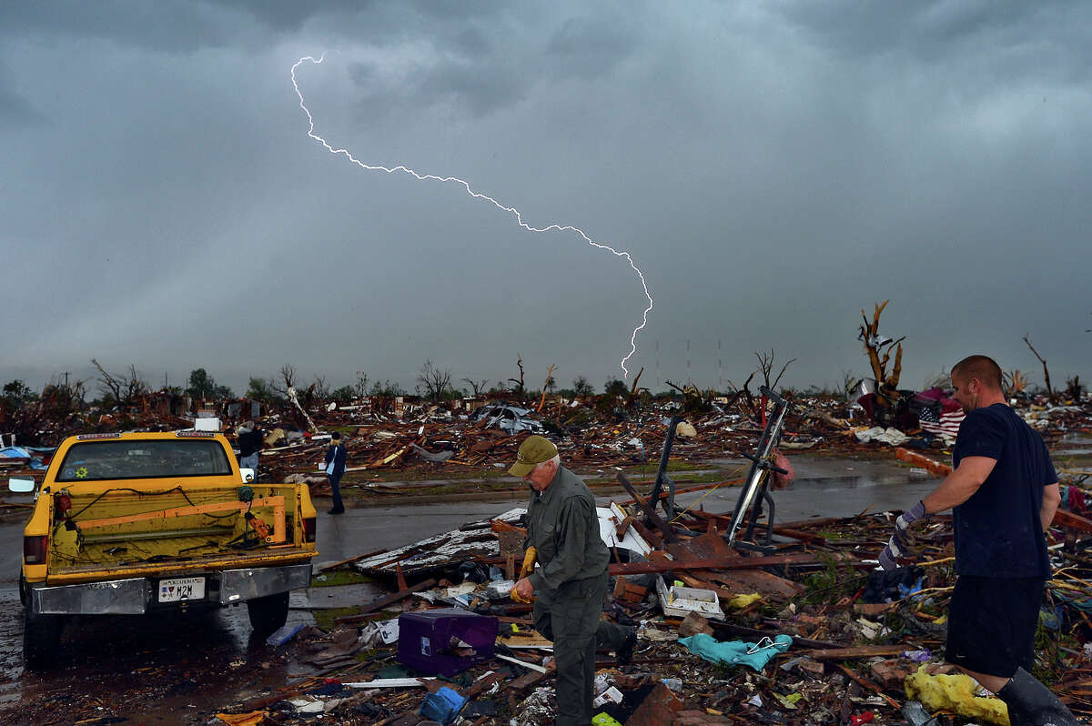 Lightning strikes during a thunder storm as tornado survivors search for salvageable stuffs at their devastated home on May 23, 2013, in Moore, Oklahoma. Severe thunderstorms barreled through this Oklahoma City suburb at dawn Thursday, complicating clean-up efforts three days after a powerful tornado killed 24 people and destroyed 2,400 homes. More rain was forecast to fall on Moore, soaking the disaster zone where residents had just the day before, under clear blue skies, started picking through the rubble of their destroyed houses to recover personal effects.