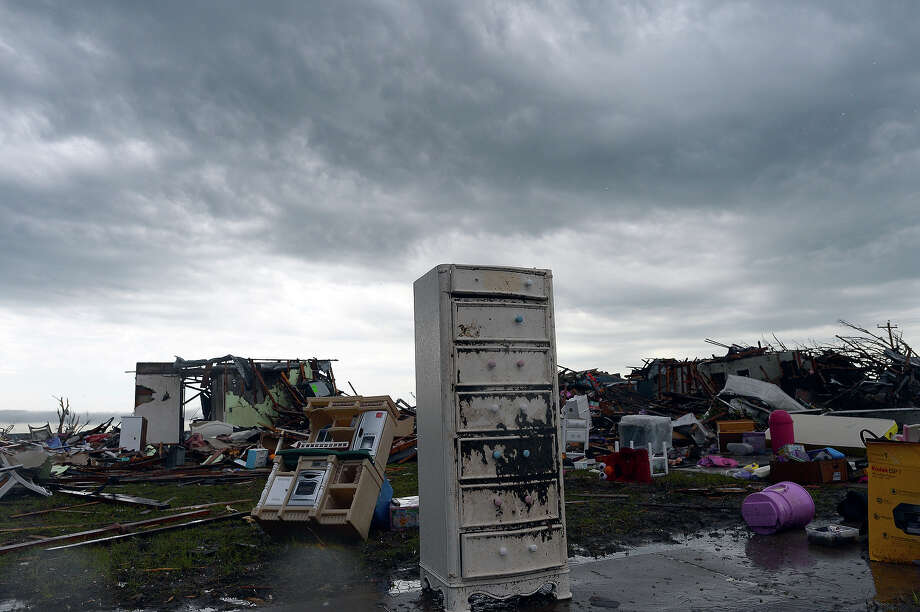 A tornado-devastated neighborhood is seen during a thunder storm on May 23, 2013 in Moore, Oklahoma. Severe thunderstorms barreled through this Oklahoma City suburb at dawn Thursday, complicating clean-up efforts three days after a powerful tornado killed 24 people and destroyed 2,400 homes. More rain was forecast to fall on Moore, soaking the disaster zone where residents had just the day before, under clear blue skies, started picking through the rubble of their destroyed houses to recover personal effects. Photo: JEWEL SAMAD, AFP/Getty Images / 2013 AFP