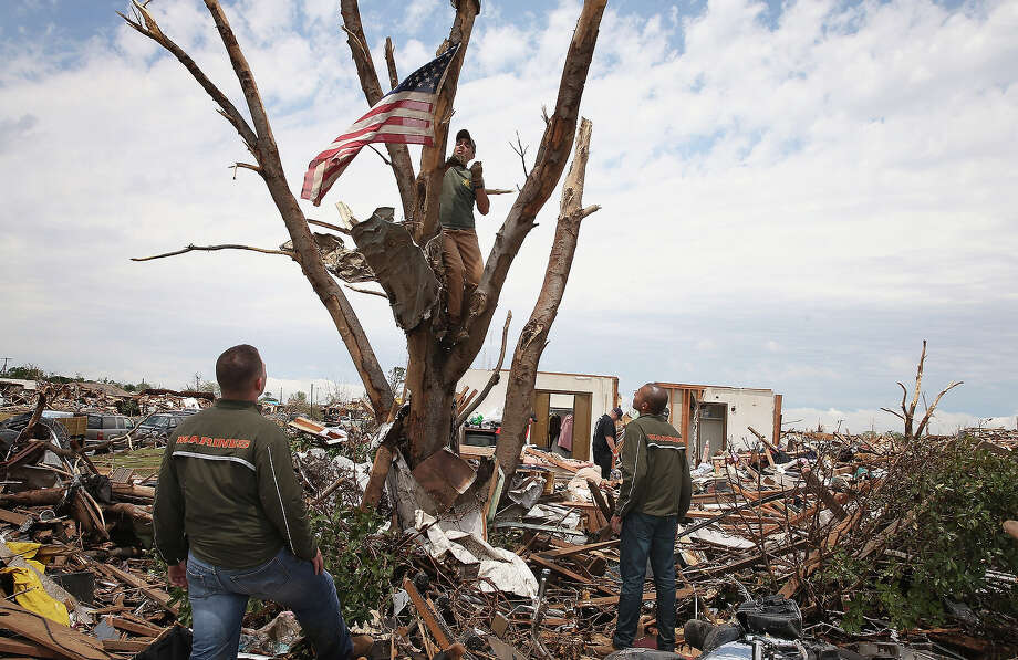 U.S. Marines Cpl. Dylan Rhodes (L) of Owasso, Oklahoma, Capt. Ray Penny (C) of Houston, TX and Cpl. Patrick Canales of Los Angeles, California recover a flag flying from a tree in front of the destroyed home of Tim Jones and Chritine Jones May 23, 2013 in Moore, Oklahoma. The flag would hang outside the Jones? home on national holidays. On Monday May 20 It was hung in a tree outside of the home after the family returned home to find their house had been leveled by a tornado and the flag tangled in the garage rafters. Today, with the help of the Marines, they decided to preserve the flag. A two-mile wide EF5 tornado touched down in Moore May 20 killing at least 24 people and leaving behind extensive damage to homes and businesses. U.S. President Barack Obama promised federal aid to supplement state and local recovery efforts. Photo: Scott Olson, Getty Images / 2013 Getty Images