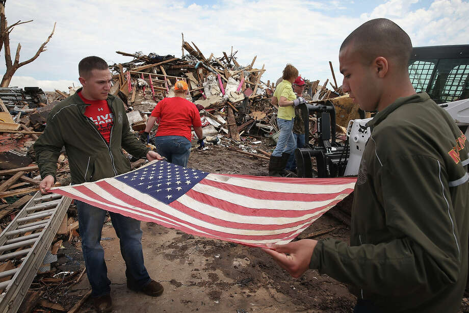 U.S. Marines Cpl. Dylan Rhodes (L) of Owasso, Oklahoma and Cpl. Patrick Canales of Los Angeles, California fold a flag for Tim Jones and Christine Jones that had been flying from a tree in front of their home, after it was destroyed by a tornado, May 23, 2013 in Moore, Oklahoma. The flag would hang outside the Jones? home on national holidays. On Monday May 20 It was hung in a tree outside of the home after the family returned home to find their house had been leveled by a tornado and the flag tangled in the garage rafters. Today, with the help of the Marines, they decided to preserve the flag. A two-mile wide EF5 tornado touched down in Moore May 20 killing at least 24 people and leaving behind extensive damage to homes and businesses. U.S. President Barack Obama promised federal aid to supplement state and local recovery efforts. Photo: Scott Olson, Getty Images / 2013 Getty Images