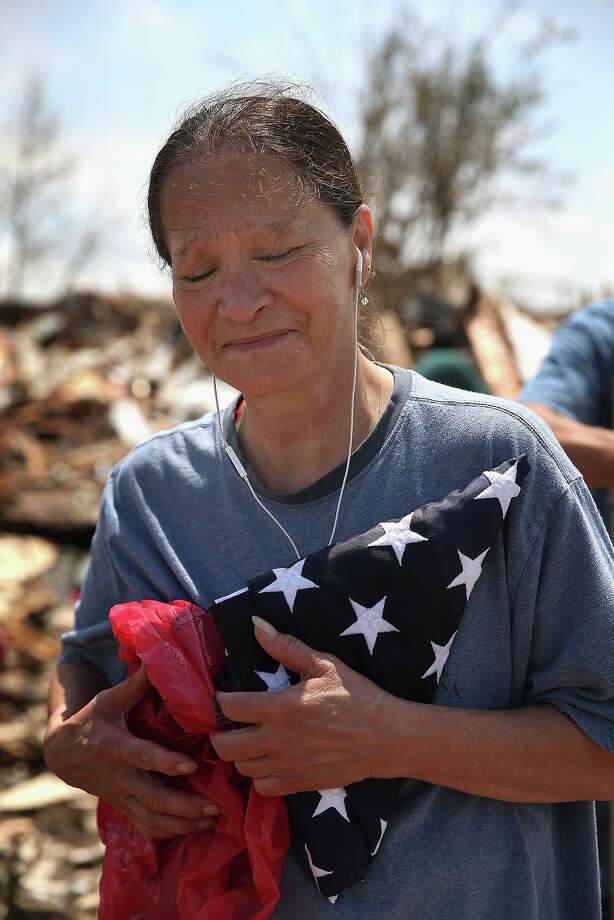 Kriket Krekemeyer fights back tears as she holds the burial flag of her father, who was a career Navy man, after it was recovered from her destroyed home on May 23, 2013 in Moore, Oklahoma. The flag was one of the most important possessions she had hoped to recover from the rubble that was once her home. A two-mile wide EF5 tornado touched down in Moore May 20 killing at least 24 people and leaving behind extensive damage to homes and businesses. U.S. President Barack Obama promised federal aid to supplement state and local recovery efforts. Photo: Scott Olson, Getty Images / 2013 Getty Images