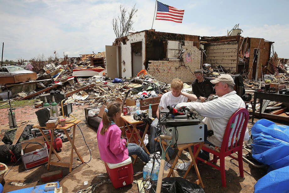 Family members take a lunch break as they help Fred Martin (not pictured) recover items from his home, which was destroyed by a tornado, on May 23, 2013 in Moore, Oklahoma. A two-mile wide EF5 tornado touched down in Moore May 20 killing at least 24 people and leaving behind extensive damage to homes and businesses. U.S. President Barack Obama promised federal aid to supplement state and local recovery efforts. Photo: Scott Olson, Getty Images / 2013 Getty Images