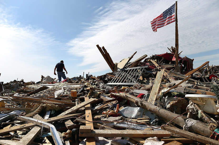 Stan Mallette searches through the rubble of his son's home on May 23, 2013 in Moore, Oklahoma. The tornado of at least EF4 strength and two miles wide touched down May 20 killing at least 24 people and leaving behind extensive damage to homes and businesses. U.S. President Barack Obama promised federal aid to supplement state and local recovery efforts. Photo: Tom Pennington, Getty Images / 2013 Getty Images