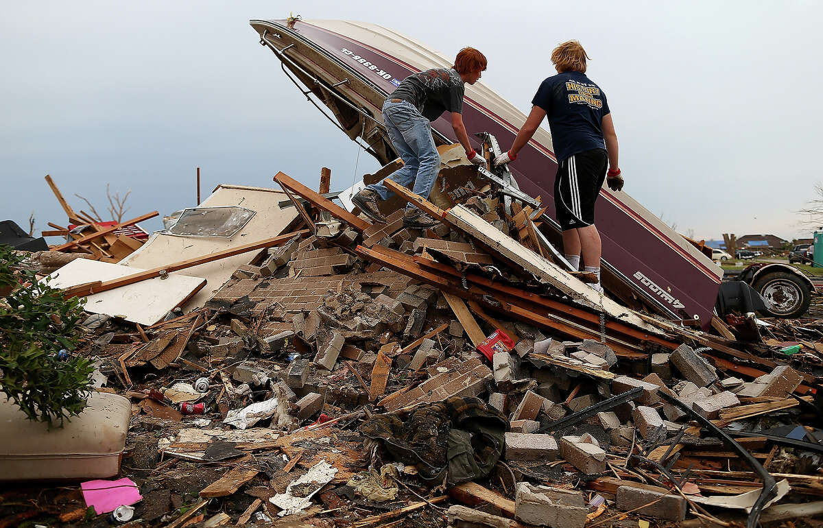 (L-R) Nathaniel Hernandez and friend John Ashcraft climb a pile of rubble to inspect a boat that belongs to the Hernandez family on May 23, 2013 in Moore, Oklahoma. The tornado of at least EF4 strength and two miles wide touched down May 20 killing at least 24 people and leaving behind extensive damage to homes and businesses. U.S. President Barack Obama promised federal aid to supplement state and local recovery efforts.