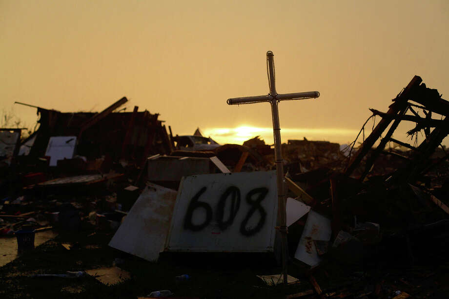 A cross stands over a destroyed home as the sun rises on May 23, 2013 in Moore, Oklahoma.  A powerful tornado classified as an EF4 passed through the town May 20, destroying homes, schools and businesses and killing 24 people including children. The epic twister, two miles (three kilometers) across, flattened block after block of homes as it struck mid-afternoon Monday, hurling cars through the air, downing power lines and setting off localized fires in a 45-minute rampage. Photo: JOSHUA LOTT, AFP/Getty Images / 2013 AFP