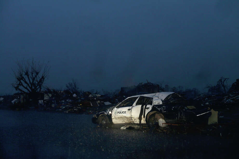 A Del City, Oklahoma police car sits in ruin on May 23, 2013 in Moore, Oklahoma. A powerful tornado classified as an EF4 passed through the town May 20, destroying homes, schools and businesses and killing 24 people including children. The epic twister, two miles (three kilometers) across, flattened block after block of homes as it struck mid-afternoon Monday, hurling cars through the air, downing power lines and setting off localized fires in a 45-minute rampage. Photo: JOSHUA LOTT, AFP/Getty Images / 2013 AFP