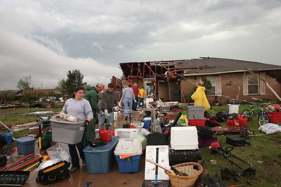 Volunteers help a co-worker to salvage belongings from her home after it was destroyed by a tornado May 23, 2013 in Moore, Oklahoma. The two-mile wide EF5 tornado touched down May 20 killing at least 24 people and leaving behind extensive damage to homes and businesses. U.S. President Barack Obama promised federal aid to supplement state and local recovery efforts. Photo: Scott Olson, Getty Images / 2013 Getty Images