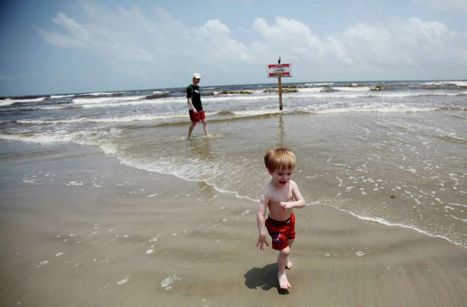 Stephen Fox chases his son Jonah Fox, 20 months, during an outing to the beach in Galveston. Photo: Mayra Beltran, Staff / © 2013 Houston Chronicle