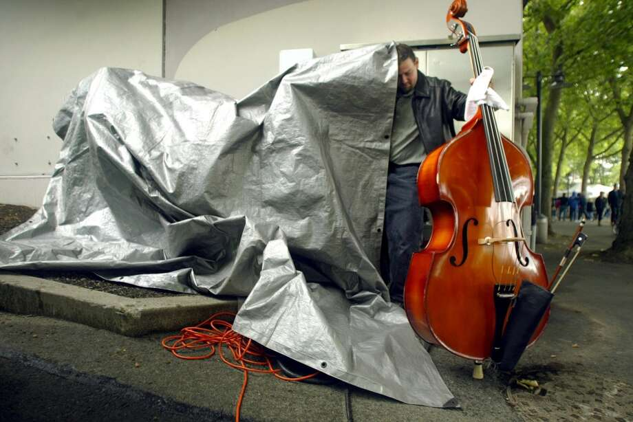 What Seattle looks like. (Photo: A musician uses a tarp to protect his contrabass from the rain at Folklife).