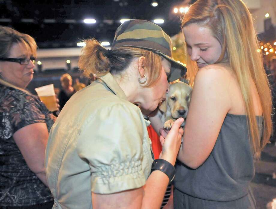 A puppy that was going to be auctioned off during the live auction at the 25th Annual Hurricane Party: Cocktails and Camo, which benefits the Red Cross, gets a kiss from Kerry Andersen, left, as Brooke Umphrey, right, holds it out to her.   Dave Ryan/The Enterprise