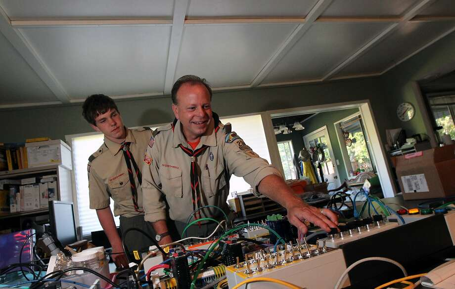 Matthias Baker 15, looks over his fathers shoulder, Wendell Baker troop 234 leader as dad explains the how his engineering prototype boards work Thursday, May 22, 2013 in Moraga Calif, Photo: Lance Iversen, The Chronicle
