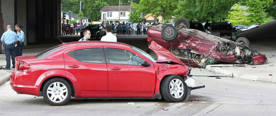 Police say the Dodge on the left was fleeing authorities when the driver ran a red light and struck the Malibu in the background, killing the woman driving it and injuring three children who were passengers. They are in serious condition. Photo: Nick De La Torre, Staff / © 2013 Houston Chronicle