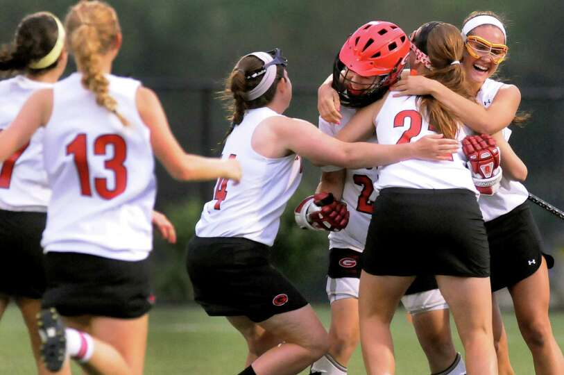 Guilderland's lacrosse players mob their goalie, Kaitlyn Hess, when they prevail over Shaker in thei