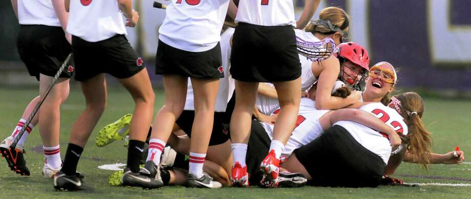 Guilderland's lacrosse players mob their goalie, Kaitlyn Hess, when they prevail over Shaker in their Section II Class A final on Thursday, May 23, 2013, at UAlbany in Albany, N.Y. (Cindy Schultz / Times Union) Photo: Cindy Schultz / 00022486A