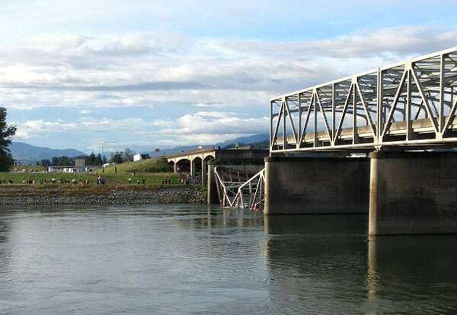 Vehicles can be seen in the water after a section of the Interstate 5 bridge over the Skagit River, north of Seattle, collapsed Thursday evening, May 23, 2013.   The four-lane bridge collapsed at about 7 p.m., Trooper Mark Francis said. Photo: AP