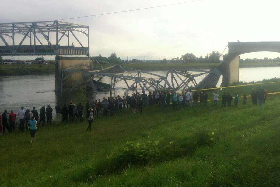 In this photo provided by NWCN, people look on after the Interstate 5 bridge collapsed over the Skagit River in Skagit County, Wash., Thursday, May 23, 2013. The four-lane bridge over the Skagit River collapsed about 7 p.m., Trooper Mark Francis said. There was no immediate estimate of how many people were in the water or whether there were any injuries or deaths, he said. Photo: AP