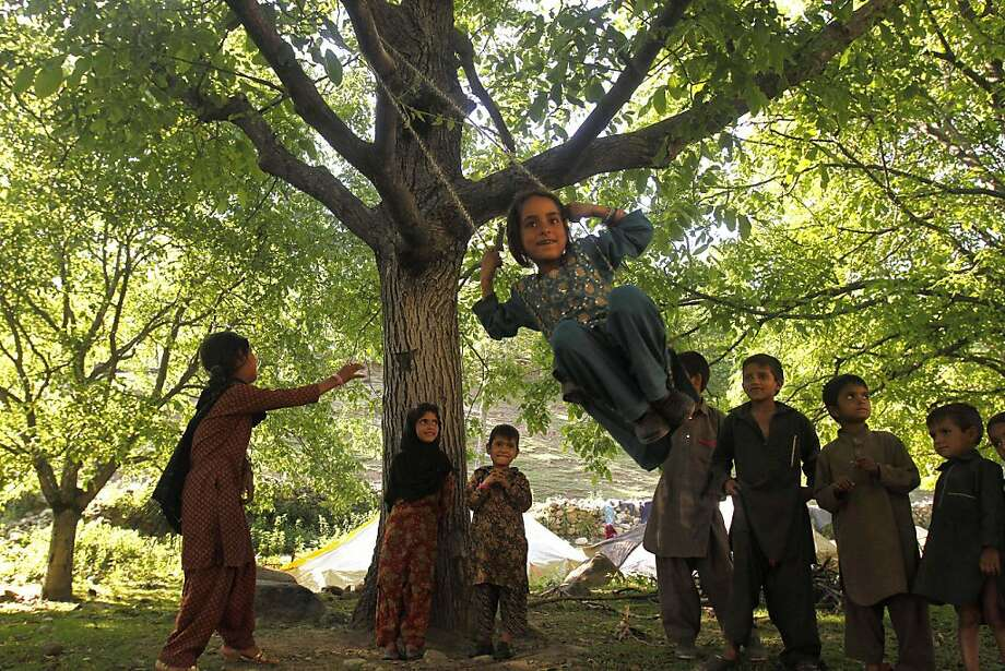 A Kashmiri Bakarwal girl plays on a swing as others wait their turn on the outskirts of Srinagar, India, Thursday, May 23, 2013. Bakarwals are nomadic herders in Jammu Kashmir state, who wander in search of good pastures for their cattle. (AP Photo/Mukhtar Khan) Photo: Mukhtar Khan, Associated Press