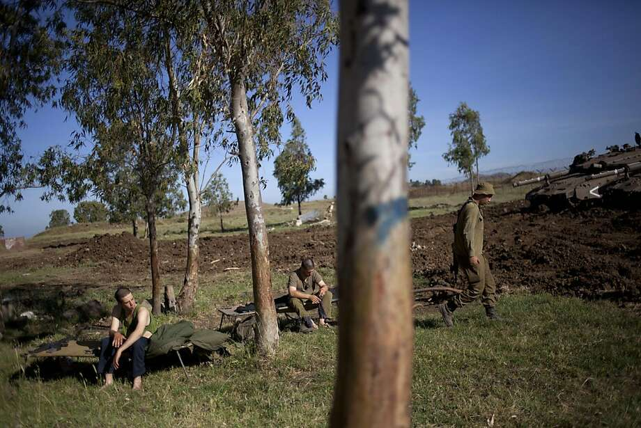 Israeli soldiers rest next to their tanks in the Israeli controlled Golan Heights, near the border with Syria, Thursday, May 23, 2013. (AP Photo/Ariel Schalit) Photo: Ariel Schalit, Associated Press