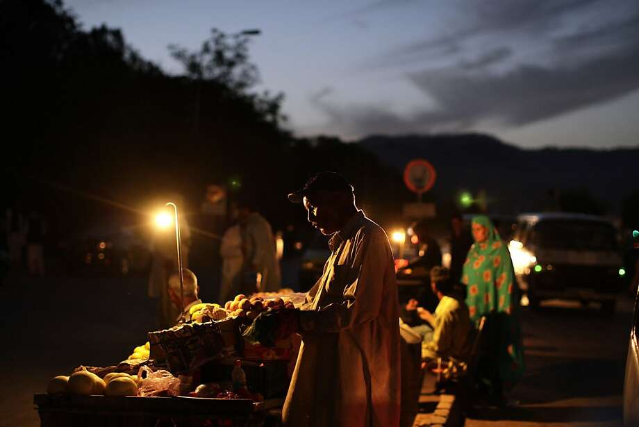 Pakistani vendors, selling fruits and food outside a hospital in Islamabad, Pakistan, use lamps to light their carts while waiting for customers on a roadside, on Thursday, May 23, 2013. (AP Photo/Muhammed Muheisen) Photo: Muhammed Muheisen, Associated Press
