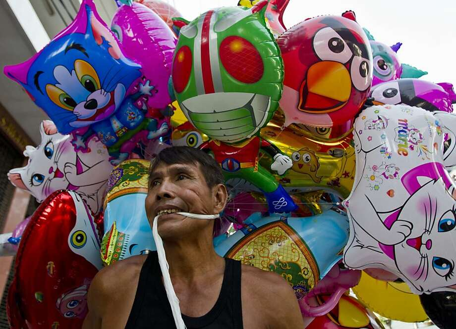 A Thai vendor carries balloons for sale in Bangkok, Thailand, Thursday, May 23 , 2013. (AP Photo/Sakchai Lalit) Photo: Sakchai Lalit, Associated Press