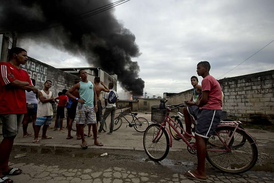 Teenagers gather to watch at fuel storage tanks burning on the northern outskirts of Rio de Janeiro, Brazil, Thursday, May 23, 2013.  A massive fire broke out Thursday at a fuel depot on the northern outskirts of Rio de Janeiro. Firefighters said in an emailed statement that no injuries had been reported yet. They evacuated a two-block area around the blaze and there was no word on a possible cause. (AP Photo/Victor R. Caivano) Photo: Victor R. Caivano, Associated Press
