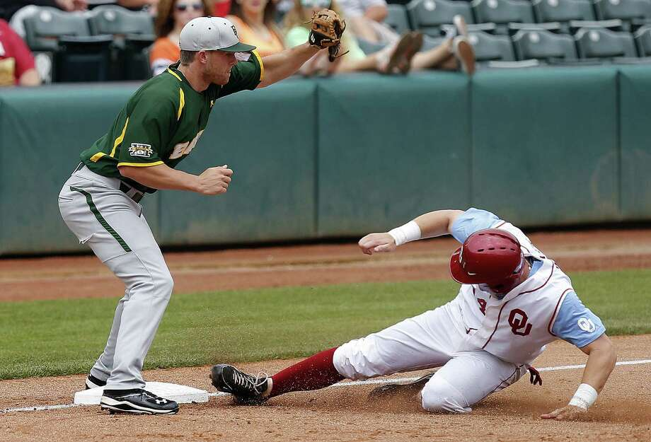 Oklahoma's Matt Oberste slides into third base ahead of the throw to Baylor's Cal Towley in the Sooners' win Thursday. Photo: Bryan Terry / Associated Press
