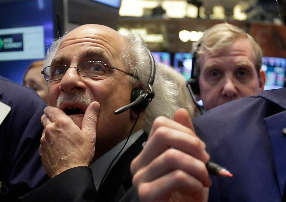 Trader Peter Tuchman, left, works on the floor of the New York Stock Exchange, Thursday, May 23, 2013. A global stock market slump is continuing on Wall Street as traders worry about how committed the Federal Reserve remains to keeping up its bond-buying program. (AP Photo/Richard Drew) Photo: Richard Drew, Associated Press