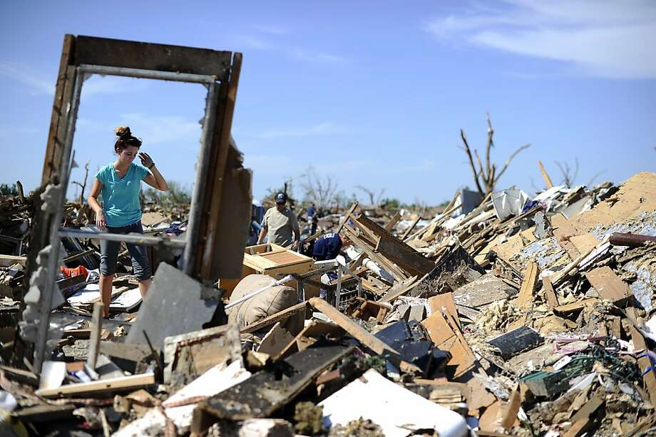 A woman searches for salvageable belongings at a tornado-devastated home on May 22, 2013 in Moore, Oklahoma. As rescue efforts in Oklahoma wound down, residents turned to the daunting task of rebuilding a US heartland community shattered by a vast tornado that killed at least 24 people. The epic twister, two miles (three kilometers) across, flattened block after block of homes as it struck mid-afternoon on May 20, hurling cars through the air, downing power lines and setting off localized fires in a 45-minute rampage. AFP PHOTO/Jewel SamadJEWEL SAMAD/AFP/Getty Images Photo: Jewel Samad, AFP/Getty Images