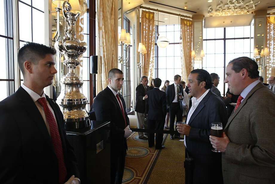 Rudi Behar, 2nd from right, and Andrew Doll, right, look over the America's Cup trophy on display before the BASHOF induction ceremony on Thursday. Bay Area sports notables gathered at the Westin St. Francis to honor the newest inductees into the Bay Area Sports Hall of Fame in San Francisco, Calif., on Thursday, May 23, 2013. New inductees include Tim Brown of the Raiders, Dave Righetti of the Giants, Walter A. Haas, Jr., and Brent Jones of the 49ers. Photo: Carlos Avila Gonzalez, The Chronicle