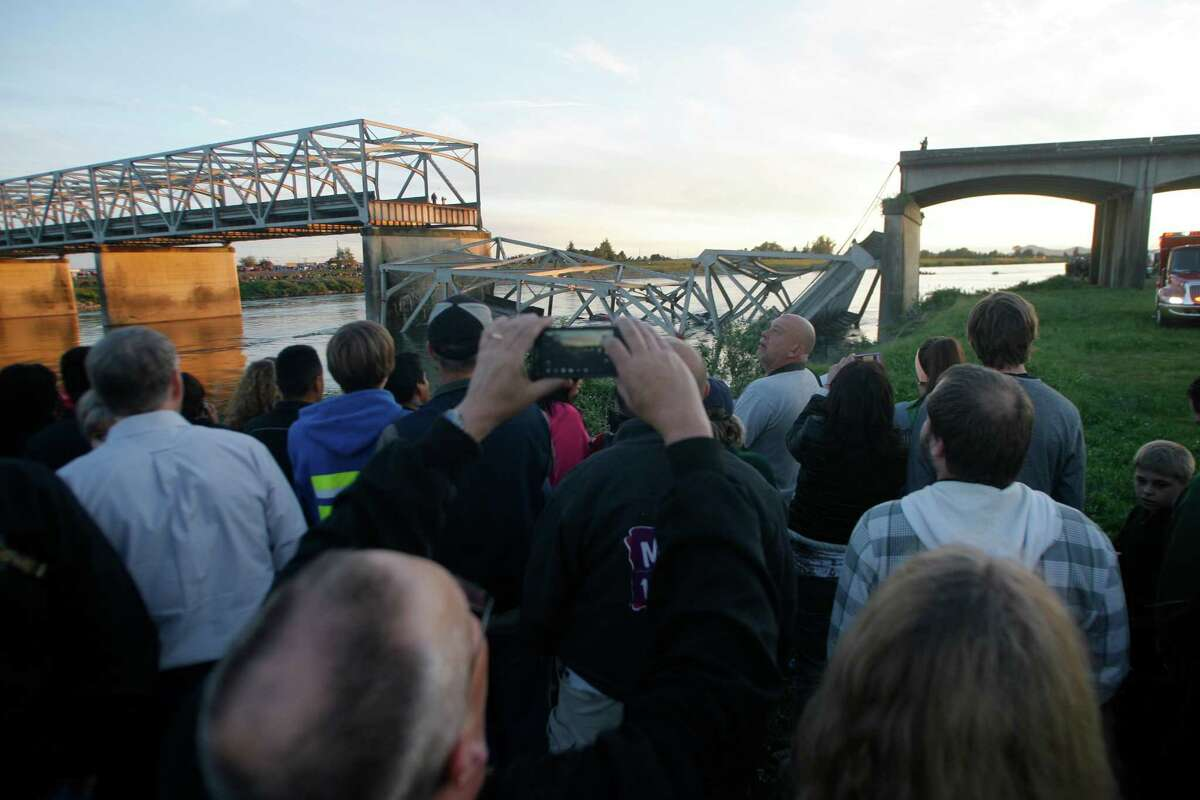 A portion of the Interstate-5 bridge is submerged after it collapsed into the Skagit River dumping vehicles and people into the water in Mount Vernon. Onlookers crowded the banks of the Skagit River and offered prayers to the victims.