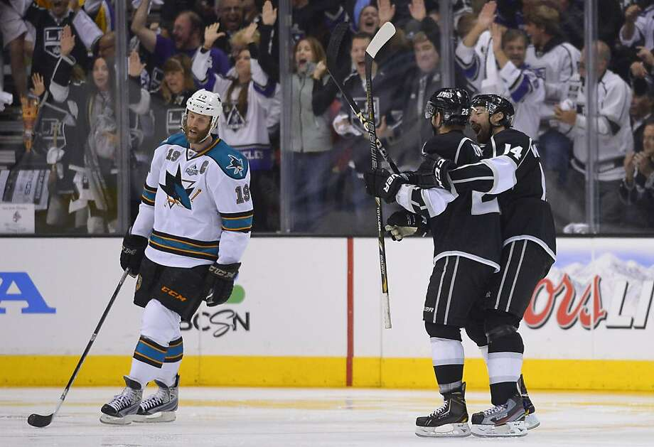 Los Angeles Kings defenseman Slava Voynov (26) is congratulated by right wing Justin Williams (14) as San Jose Sharks center Joe Thornton (19) skates by after Voynov scored during the third period in Game 5 of the Western Conference semifinals in the NHL hockey Stanley Cup playoffs, Thursday, May 23, 2013, in Los Angeles.  (AP Photo/Mark J. Terrill) Photo: Mark J. Terrill, Associated Press