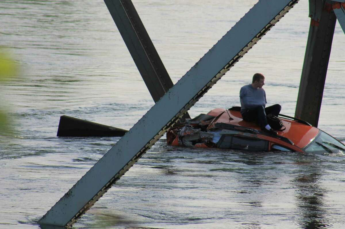 A man sits on his car after an Interstate 5 bridge collapsed over the Skagit River between Mt. Vernon and Burlington on Thursday, May 23, 2013. Two cars and one travel trailer went in the water. There were no known fatalities.