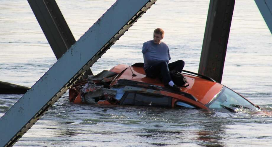 In this photo provided by Francisco Rodriguez, a man is seen sitting atop a car that fell into the Skagit River after the collapse of the Interstate 5 bridge there minutes earlier Thursday, May 23, 2013, in Mount Vernon, Wash. Photo: Francisco Rodriguez, Associated Press