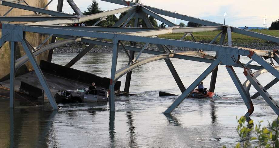 In this photo provided by Francisco Rodriguez, one man is seen sitting atop a car that fell into the Skagit River another stands in the door of his partially submerged pickup truck after the collapse of the Interstate 5 bridge there minutes earlier Thursday, May 23, 2013, in Mount Vernon, Wash. Photo: Francisco Rodriguez, Associated Press