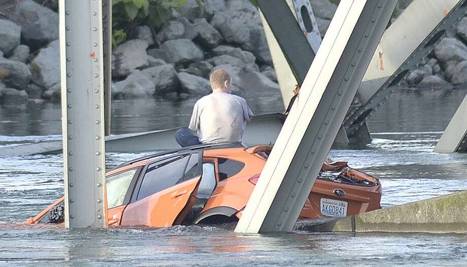 An unidentified man waits on his submerged vehicle in the Skagit River Thursday May 23, 2012. The Interstate 5 bridge over the Skagit river collapsed north of Seattle Thursday evening, dumping two vehicles into the water and sparking a rescue effort by boats and divers as three injured people were pulled from the chilly waterway. Photo: Frank Varga, Associated Press