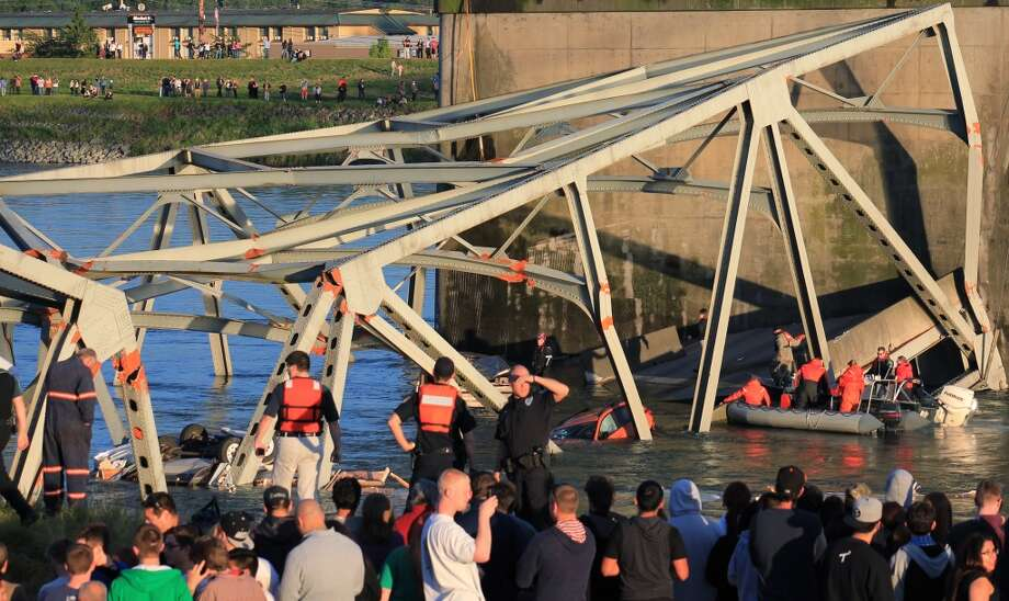 In this photo provided by Francisco Rodriguez, rescue workers surround the scene where a pickup truck and a car fell into the Skagit River after the collapse of the Interstate 5 bridgeThursday, May 23, 2013, in Mount Vernon, Wash. Photo: Francisco Rodriguez, Associated Press