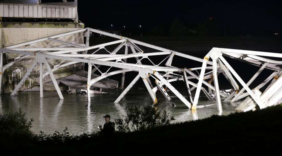 A police officer walks along the bank near the collapsed Interstate-5 bridge submerged after collapsing into the Skagit River, dumping vehicles and people into the water, in Mount Vernon, Wash., Thursday, May 23, 2013. Photo: Elaine Thompson, Associated Press