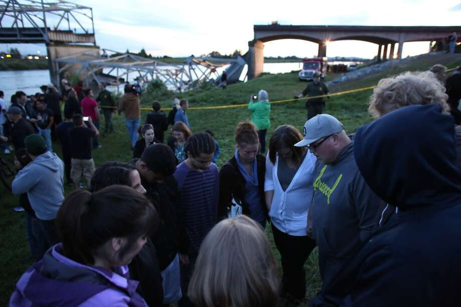 People offer spontaneous prayer after an Interstate 5 bridge collapsed over the Skagit River between Mt. Vernon and Burlington, Wash. on Thursday, May 23, 2013. Two cars and one travel trailer went in the water. There were no know fatalities. Photo: Joshua Trujillo, Seattlepi.com