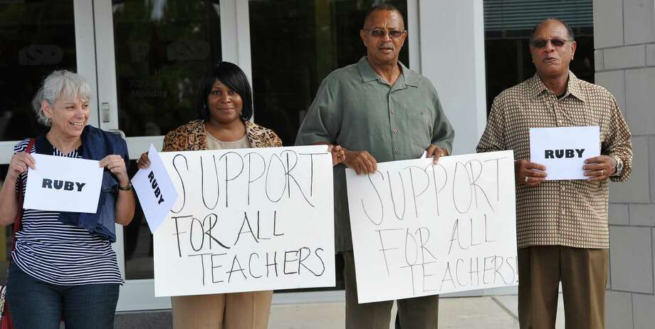 Edna Haley, and her husband Nathan, center couple, and others hold signs in support of the Port Arthur teacher.  Teachers and friends from around the area gathered outside of the Port Arthur Independent School District Administration building Thursday night before the board meeting to show their support  of Ruby Gunner.  Gunner has been suspended by the board after being accused of attacking a fourth grade student.  Dave Ryan/The Enterprise