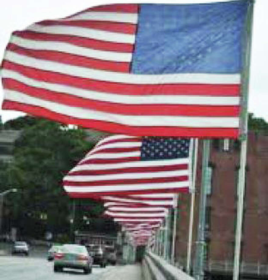 Flags festooning the Post Road bridge over the Saugatuck River will fly in salute to the town's Memorial Day parade on Monday. Photo: File Photo / Fairfield Citizen