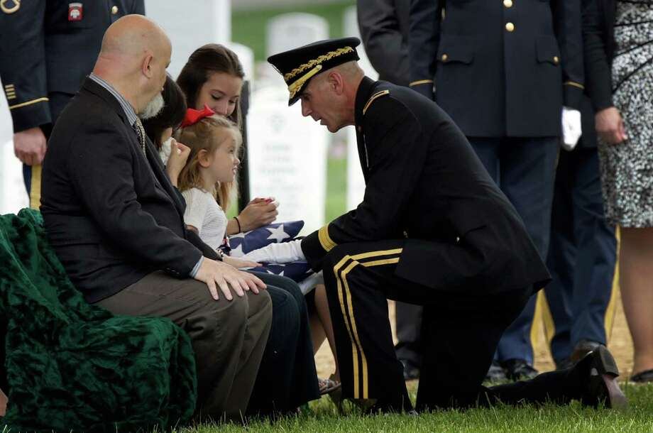 Four-year-old Sophia Phillips is presented an American flag by Brigadier Gen. James Pasquarette during a burial service for her father, Staff Sgt. Francis G. Phillips, at Arlington National Cemetery on Monday, May 20. The Meridian, N.Y. soldier was killed in Afghanistan when the vehicle he was riding in was struck by an improvised explosive device. Photo: Win McNamee, Getty Images / 2013 Getty Images