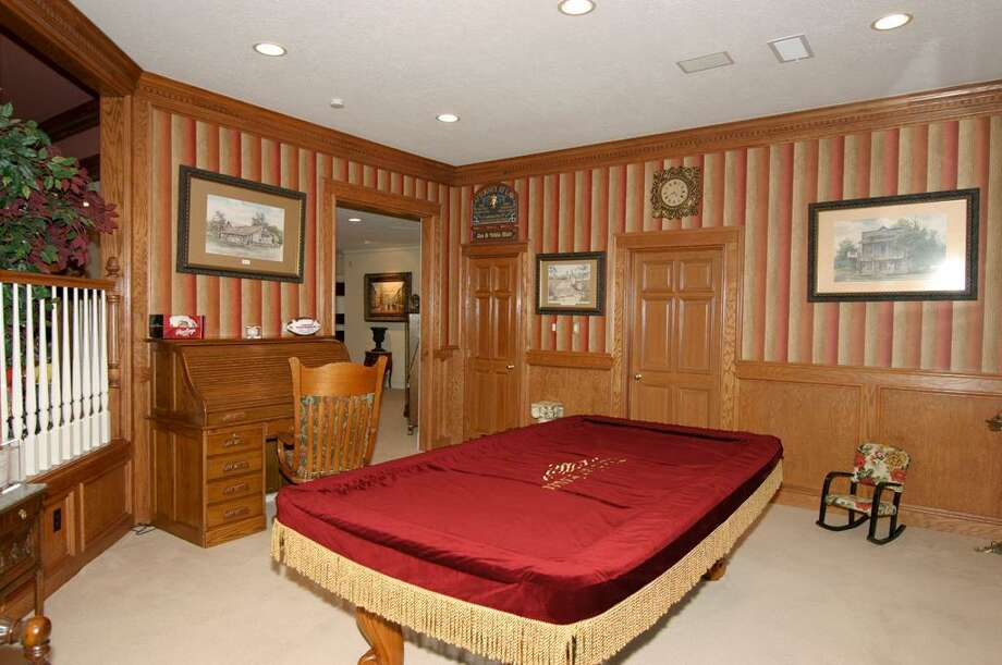 Adjacent to the game room is the billiards room, with wood paneling, ventable windows and two large storage closets. Photo: HAR.com