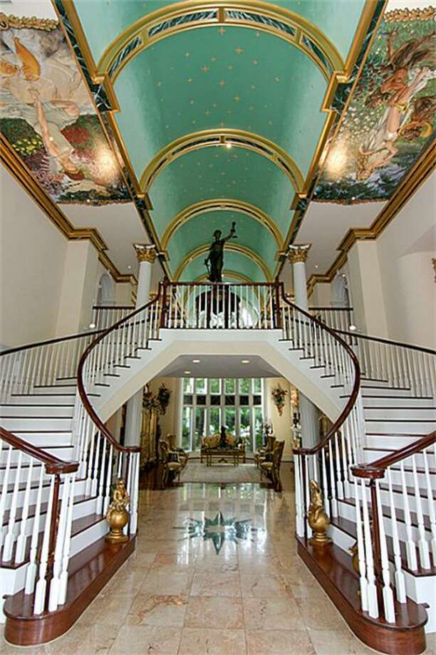 Enter through custom leaded glass front doors and gaze up to the grand curved double stairway. Foyer ceiling with hand painted murals depict the four seasons - so beautiful! Photo: HAR.com