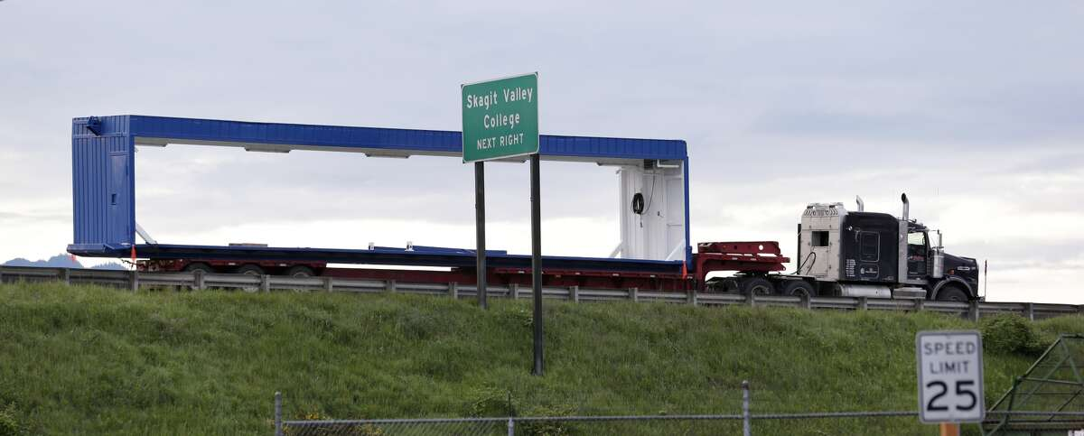 A truck that was carrying an oversize load sits parked southbound on Interstate 5 immediately south of the collapsed portion of the highway bridge at the Skagit River Friday, May 24, 2013, in Mount Vernon, Wash. The Washington State Patrol says the truck was hauling a too-tall load of drilling equipment from Canada to Vancouver, Wash., when it hit an overhead bridge girder on the major interstate between Seattle and Canada, sending a section of the span and two vehicles into the Skagit River Thursday evening. All three occupants suffered only minor injuries. (AP Photo/Elaine Thompson) Summary